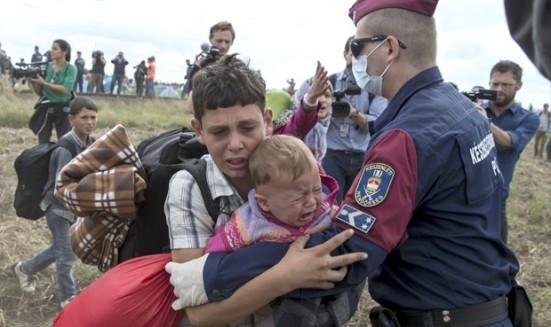 Un policía en la frontera de Hungría con Serbia intenta detener a un muchacho sirio con su pequeño hermano en brazos.  Reuters